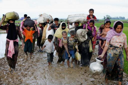 A group of Rohingya refugees walk on the muddy road after travelling over the Bangladesh-Myanmar border in Teknaf